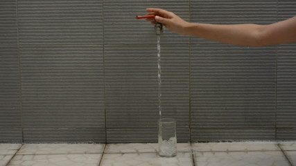 hand Filling glass of water for drinking water