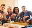 Group of multi ethnic friends with pizza and bottles of drink