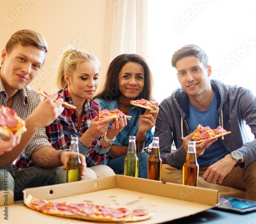 Group of multi ethnic friends with pizza and bottles of drink  - 64476502
