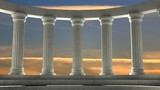 Ancient marble pillars in elliptical arrangement with orange sky