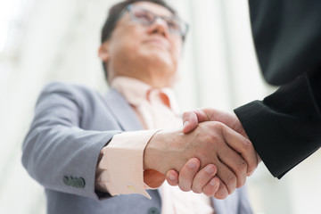 Asian business men handshaking