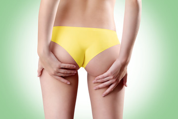 Bum and legs of woman, hands touching the buttocks over green ba