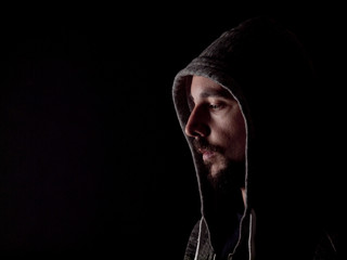 Low key image of a bearded man with a hoody