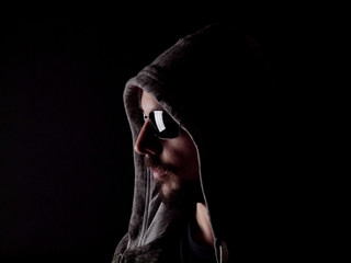 Low key image of a bearded man with a hoody and sunglasses