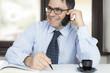 Uomo in ufficio contento al telefono