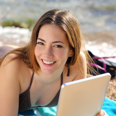 Pretty happy woman using a tablet on the beach