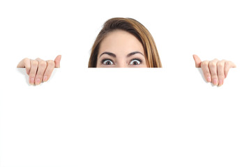 Surprised woman eyes over a blank promotional display