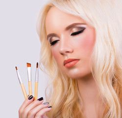 Beautiful blonde girl with makeup brushes