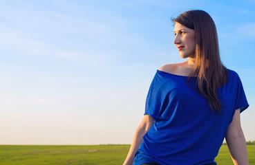 Красивая женщина на фоне зеленой равнины и голубого неба