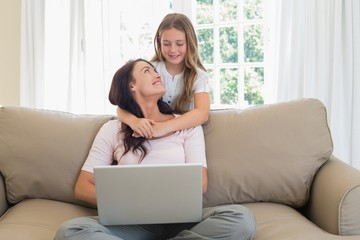 Little girl embracing mother using laptop on sofa