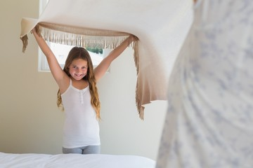 Happy little girl making bed with mother