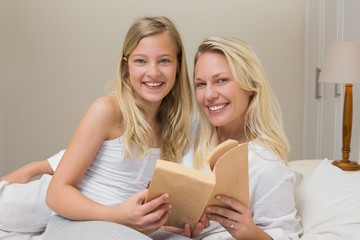 Mother and daughter holding story book in bed