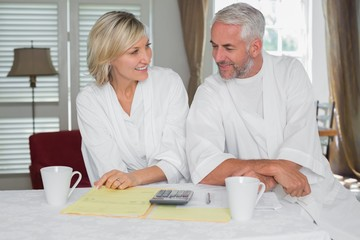 Casual mature couple with home bills and calculator