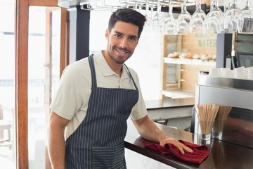 Smiling waiter cleaning countertop with sponge