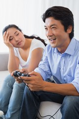 Woman being ignored by boyfriend playing video games