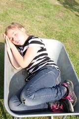 Schlafendes Mädchen in Schubkarre