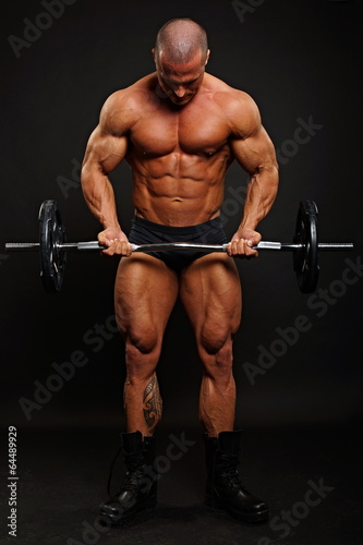 Muscular man standing poses with dumbbell on gray background - 64489929
