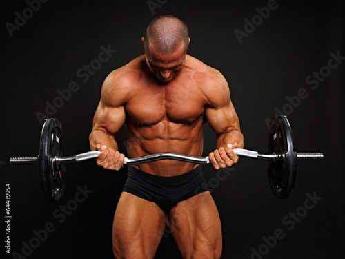 Portrait of muscular man with dumbbell on gray background - 64489954