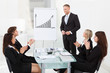 Businesspeople Clapping For Colleague After Presentation