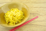 Big yellow noodle scald in brown bowl and chopsticks poster