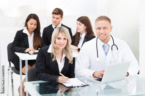 Smiling Male Doctor And Businesswoman With Laptop