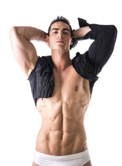 Muscular young man with single-sleeved shirt on naked torso
