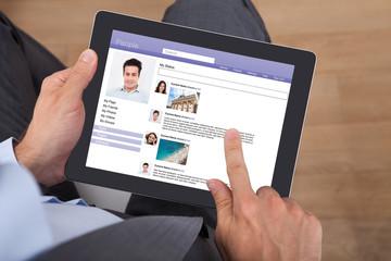 Businessman Surfing Social Networking Site On Digital Tablet