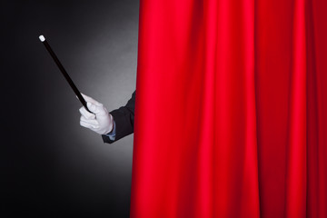 Magician Holding Wand Behind Stage Curtain