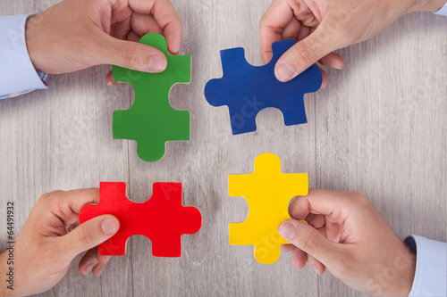 Businesspeople Joining Multicolored Puzzle Pieces At Desk