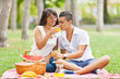 Young happy couple having picnic in the park.