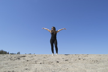 Beautiful woman on the top (beach, sand, raised arms)