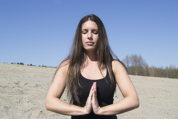 Beautiful woman meditating in the sunshine (beach, portrait)