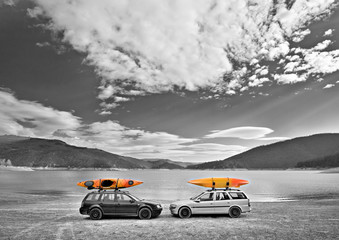 Kayaks on cars in front of a lake