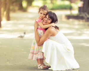 Beautiful portrait of little daughter embracing her mommy.