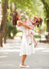 Beautiful portrait of little daughter playing with her mommy.