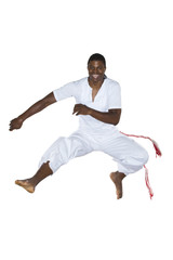 Capoeira, Brazilian Man jumping, dressed in white.