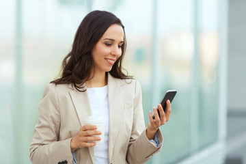 Businesswoman taking a coffee break and using smartphone.