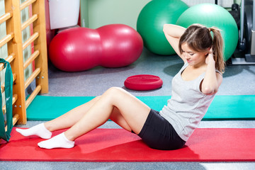 Girl doing crunches on gym mat