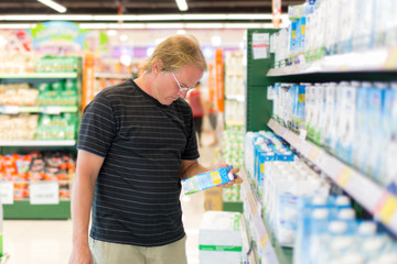 man buys milk at the supermarket