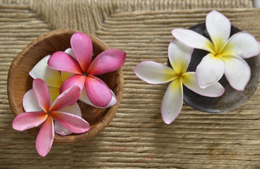 White and pink frangipani in water bowl on Brown straw mat