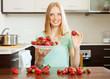 housewife with strawberries at  kitchen