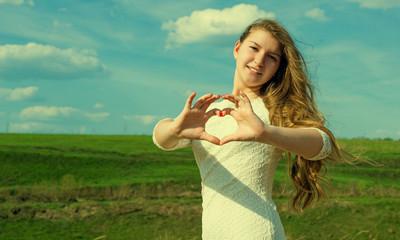 Красивая девушка показывает руками сердце на фоне природы