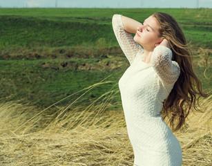Красивая девушка насаждается свободой среди зеленых полей