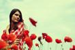 Portrait of calm beautiful girl through a poppy field, summer ou