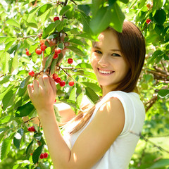 portrait of pretty cheerful young girl in cherry garden