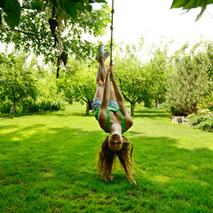Happy excited teen girl on a rope swing, summer park outdoor