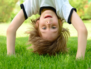 Happy little boy standing upside down on green grass in spring p