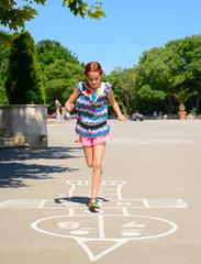 hopscotch, girl jumps in summer park outdoor
