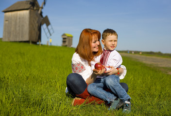 Mother with child on a grass in Ukrainian national clothes