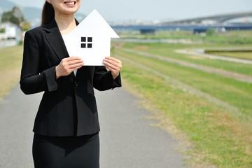 野外で住宅の模型を持って家を紹介するスーツの女性